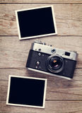 Vintage film camera and two blank photo frames. On wooden table. Top view Stock Images