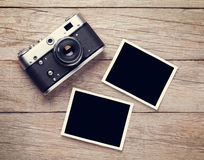 Vintage film camera and two blank photo frames. On wooden table. Top view Stock Image