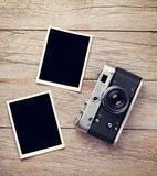 Vintage film camera and two blank photo frames. On wooden table. Top view Royalty Free Stock Image