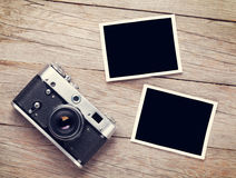 Vintage film camera and two blank photo frames. On wooden table. Top view Royalty Free Stock Photo