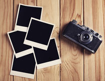 Vintage film camera and two blank photo frames on wooden table. Top view photo Stock Image