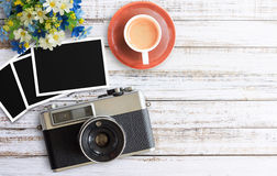 Vintage film camera and two blank photo frames on wooden table. Top view with copy space for design Royalty Free Stock Images