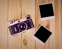 Vintage film camera and two blank photo frames on wooden table. Top view photo shot Stock Photo