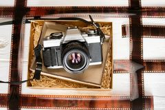 Vintage film camera in a wooden box on wooden white background with film Royalty Free Stock Image