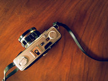 Vintage film camera in yellow light and a little green shadow. Royalty Free Stock Images
