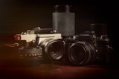 Vintage film cameras and lenses. On a dark background Royalty Free Stock Photography