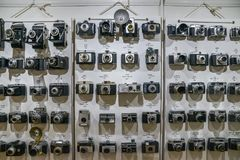 Vintage film cameras lined up on wall in chronological order starting from 1920s to 1960s showing technological. London, UK - Mar 6, 2018: Vintage film cameras Stock Photo