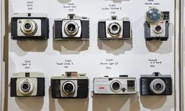 Vintage film cameras lined up on wall in chronological order starting from 1959 to 1961 showing technological evolution. London, UK - Mar 6, 2018: Vintage film Royalty Free Stock Photo