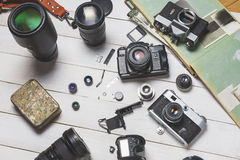 Vintage film cameras, their components, modern digital cameras and lenses on wooden white background  technology development conce Royalty Free Stock Image