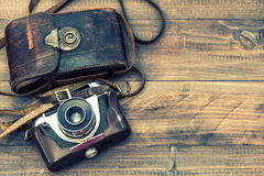 Vintage film photo camera with leather bag on wooden background. Top view. Retro Instagram style toned picture Royalty Free Stock Photography