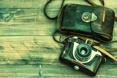 Vintage film photo camera with leather bag on wooden background Stock Photos