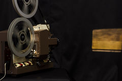 Vintage film projector. Dark background with projection Stock Photos