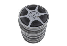 Vintage Film Reel and Cans Stacked. Vintage movie reel and film cans stacked high and isolated Royalty Free Stock Photo