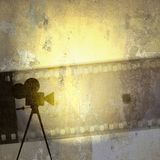 Vintage film strip background and old cinecamera. Vintage sepia film strip background and old cinecamera Stock Photo