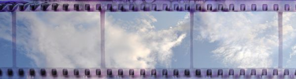 Vintage film strip frame with clear cloudy sky. Retro design element Royalty Free Stock Images