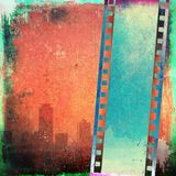 Vintage film strip on red grunge city skyline. With copy space Stock Photos
