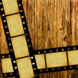 Vintage film on wood. Vintage grungy negative film stripes on old wooden background Stock Photos