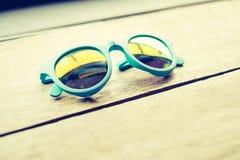 Vintage filter,blue sun glasses on wood plank table Stock Photos