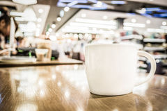 Vintage filter, White coffee cup on wood table with blurred cafe Royalty Free Stock Photography