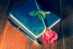 Vintage filtered artificial rose with note book and pen. Royalty Free Stock Photography