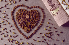 Vintage filtered coffee beans in a shape of a heart on canvas Royalty Free Stock Photos