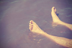 Vintage filtered male bare feet in lake water. Stock Photo