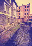 Vintage filtered photo of ruined building by the river. Royalty Free Stock Photos