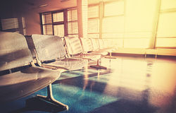 Vintage filtered picture of empty airport waiting room at sunrise stock image