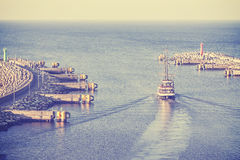 Vintage filtered picture of old ship leaving port. Royalty Free Stock Image