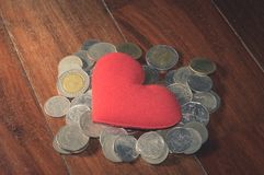 Vintage color, red heart on coins heap. Royalty Free Stock Images
