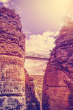 Vintage filtered steel bridge between rocks. Royalty Free Stock Photography