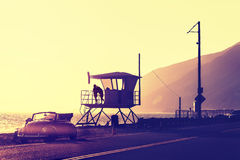 Vintage filtered sunset over beach with lifeguard tower. Royalty Free Stock Images