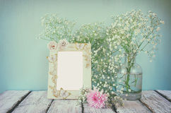 Vintage filtered and toned image of image of pink and white flowers and antique frame on wooden table. template Stock Photos