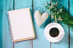 Vintage filtered and toned top view image of daisy flowers, blank notebook and fabric heart next to cup of coffee Stock Photography