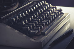 Vintage filtered Typewriter and pen on table. Stock Image