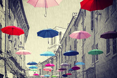 Vintage filtered umbrellas hanging above street. Royalty Free Stock Photo