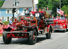 Vintage Fire Engine. Antique Fire Engine rolls down the road during the 2011 Bristol 4th of July Parade in Bristol, Rhode Island Royalty Free Stock Image