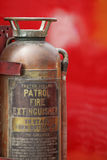 Vintage Fire Extinguisher. Antique fire extinguisher on red background- room for text on right Stock Photography