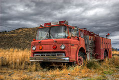 Vintage fire truck. A vintage red fire truck on the field Stock Photos