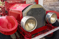 Vintage Firetruck. A vintage firetruck with large headlamps stands beside an old stone building once used as a firehouse in a westernl town Royalty Free Stock Photos