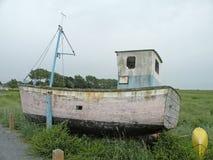 Vintage fishing boat. Abandoned fishing boat on dry land on the coast of France Stock Images