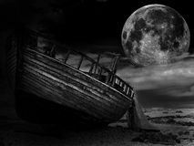 Vintage fishing boat. An old abandoned fishing boat stranded on a beech in black and white Royalty Free Stock Images