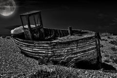 Vintage fishing boat. An old abandoned fishing boat stranded on a beech in black and white Royalty Free Stock Image