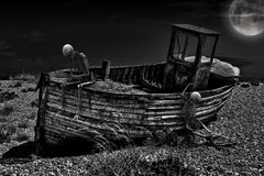 Vintage fishing boat. An old abandoned fishing boat stranded on a beech with two skeletons in black and white Royalty Free Stock Photography