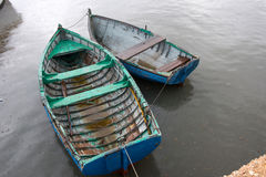 Fishing boats on water. Vintage fishing boats on water in a rainy day Royalty Free Stock Photos