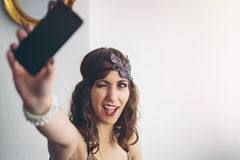 Vintage flapper girl using a modern smartphone for a selfie Stock Image