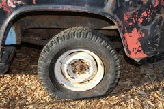 Vintage flat tire on retro truck parked on wood chips stock photos