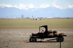 Vintage flatbed truck with hay bales in a farm field. This is a vintage flatbed truck with hay bales on the back area.  The vehicle is parked in a farm field in royalty free stock images