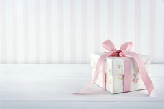Vintage floral pattern gift box. Floral pattern gift box tied with pink ribbon on white wooden background with copy space Royalty Free Stock Photo