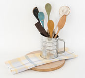 Vintage Flour Sifter with Wooden Spoons Kitchen Scene. Vintage metal flour sifter with assorted wooden spoons kitchen scene Stock Photos